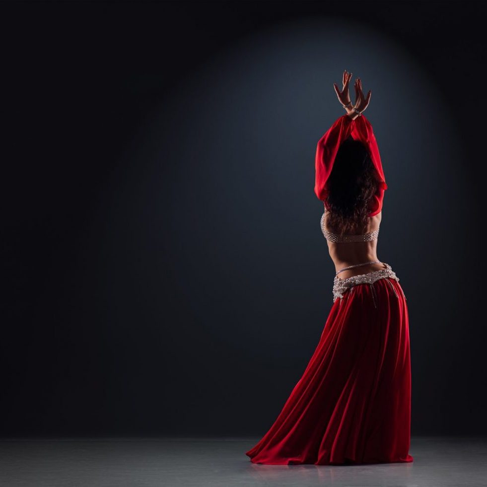 beautiful black-haired girl in a red ethnic dress on the stage dances oriental dancing with her back